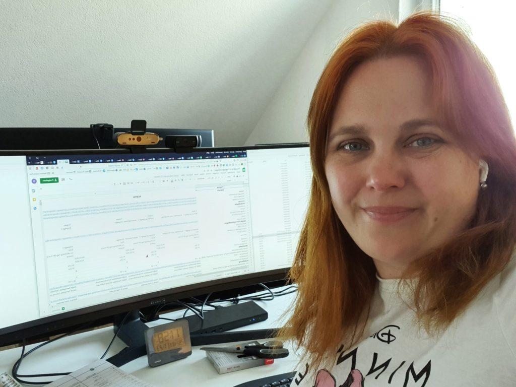 Sandra am Schreibtisch mit einer Excel-Tabelle auf dem Monitor